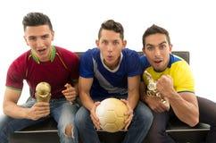 Trois amis s'asseyant sur les chemises de sports de port de sofa, tenant la boule et encourager criard de trophée à l'appareil-ph Image libre de droits