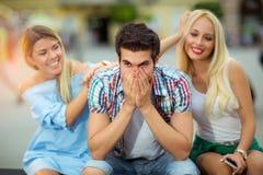 Trois amis s'asseyant sur un banc et ayant l'amusement Photos libres de droits