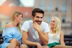 Trois amis s'asseyant sur un banc et ayant l'amusement Image libre de droits