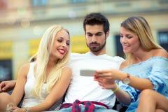 Trois amis s'asseyant sur un banc et regardant le téléphone Images libres de droits