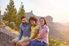 Trois amis s'asseyant sur un mur en pierre Photos stock