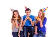Trois amis s'asseyant sur un sofa et mangeant de la pizza Images libres de droits