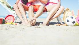 Trois amis s'asseyant sur une plate-forme de plage Photo stock