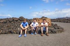 Trois amis s'asseyant sur une roche et ont un reste Photo stock