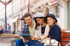 Trois amis s'asseyent ainsi que le comprimé sur le banc Image libre de droits