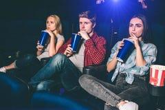 Trois amis s'asseyent ensemble et coke potable en même temps Ils observent le film Les jeunes sont sérieux Image stock