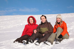 Trois amis s'asseyent sur la neige Image libre de droits