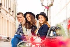 Trois amis s'asseyent sur le banc dans la belle rue Image libre de droits