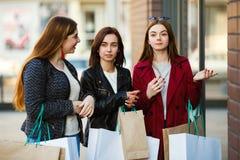 Trois amis se sont arrêtés près de la fenêtre de boutique Image libre de droits
