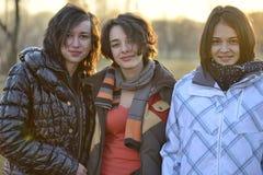 Trois amis se tenant ensemble pendant le coucher du soleil Image libre de droits
