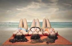 Trois amis se trouvant à la plage Image libre de droits