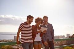 Trois amis souriant à un comprimé Images stock