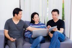 Trois amis sur la ligne avec les dispositifs multiples et se reposer parlant sur le sofa Images stock
