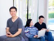 Trois amis sur la ligne avec les dispositifs multiples et se reposer parlant sur un sofa dans le salon dans une maison Photos libres de droits