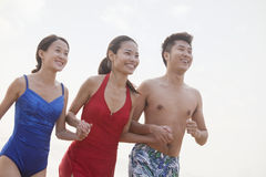 Trois amis tenant des mains et souriant sur la plage Photographie stock