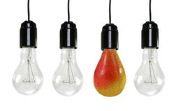 Trois ampoules électriques et une poire Image stock