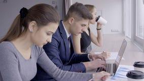 Trois analytics financiers analysent des tendances de bitcoin se reposant à la barre en bois en café clips vidéos