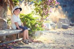 Trois années de garçon s'asseyant sur le banc Image libre de droits