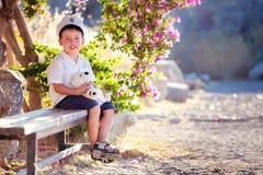 Trois années de garçon s'asseyant sur le banc Photos stock