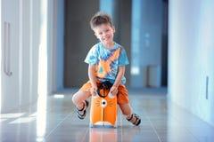 Trois années mignonnes de garçon s'asseyant sur une valise Photographie stock