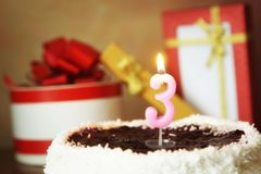 Trois ans d'anniversaire Gâteau avec la bougie et les cadeaux brûlants Photographie stock libre de droits