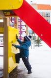 Trois ans de bébé garçon jouant sur le terrain de jeu en hiver Image stock