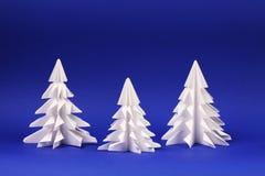 Trois arbres de livre blanc sur les arbres bleus d'origami de fond Photographie stock