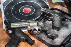 Trois armes à feu et cibles sur la table dehors photographie stock
