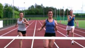 Trois athlètes courant vers la ligne d'arrivée banque de vidéos