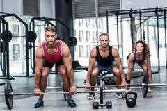 Trois athlètes musculaires soulevant un barbell Photographie stock libre de droits