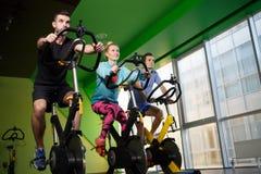 Trois athlètes sur des vélos d'exercice Photographie stock libre de droits