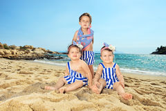 Trois bébés s'asseyant sur une plage sablonneuse Image libre de droits