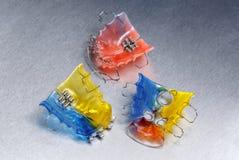 Trois bagues dentaires ou arrêtoirs colorés pour des dents sur le fond de metall Image stock