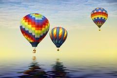 Trois ballons à air chauds au-dessus de l'eau Photo stock