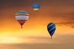 Trois ballons à air chauds en vol sur le ciel de coucher du soleil Images libres de droits