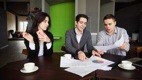 Trois banquiers, types et amies responsables travaillent avec des documen Image libre de droits