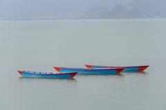 Trois bateaux bleus sur le lac Phewa dans Pokhara Photographie stock libre de droits