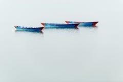 Trois bateaux bleus sur le lac Phewa dans Pokhara Photographie stock
