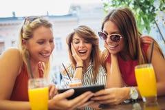 Trois beaux amis dans un café utilisant le PC de comprimé Images libres de droits