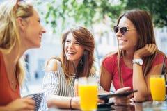 Trois beaux amis dans un café utilisant le PC de comprimé Photo stock