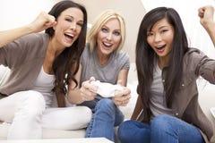 Trois beaux amis de femmes jouant des jeux vidéo Photo libre de droits
