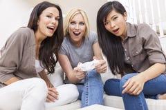 Trois beaux amis de femmes jouant des jeux vidéo à la maison Image stock