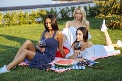 Trois beaux amis de jeunes femmes appréciant un pique-nique sur une pelouse verte Photos libres de droits
