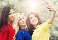 Trois beaux amis féminins étant modernes en prenant des selfies Image libre de droits