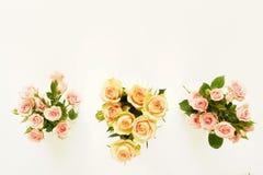 Trois beaux bouquets des roses roses et crèmes dans des vases blancs Photos libres de droits
