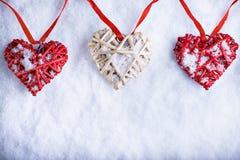 Trois beaux coeurs romantiques de vintage accrochent sur une bande rouge sur un fond blanc de neige Amour et concept de jour de v Photographie stock