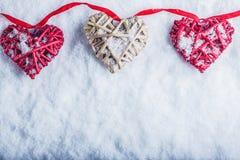 Trois beaux coeurs romantiques de vintage accrochent sur une bande rouge sur un fond blanc de neige Amour et concept de jour de v Photos stock