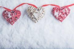 Trois beaux coeurs romantiques de vintage accrochent sur une bande rouge sur un fond blanc de neige Amour et concept de jour de v Photo stock