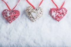 Trois beaux coeurs romantiques de vintage accrochent sur une bande rouge sur un fond blanc de neige Amour et concept de jour de v Images stock
