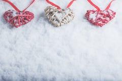Trois beaux coeurs romantiques de vintage accrochent sur une bande rouge sur un fond blanc de neige Amour et concept de jour de v Photo libre de droits
